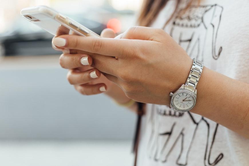 Mãos de mulher segurando um smartphone.