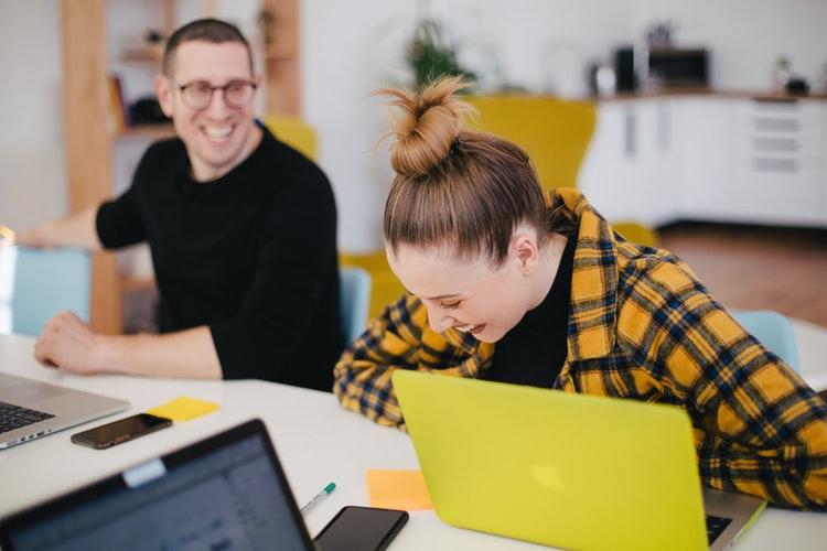 Homem e mulher sorrindo enquanto trabalham em frente aos seus computadores.