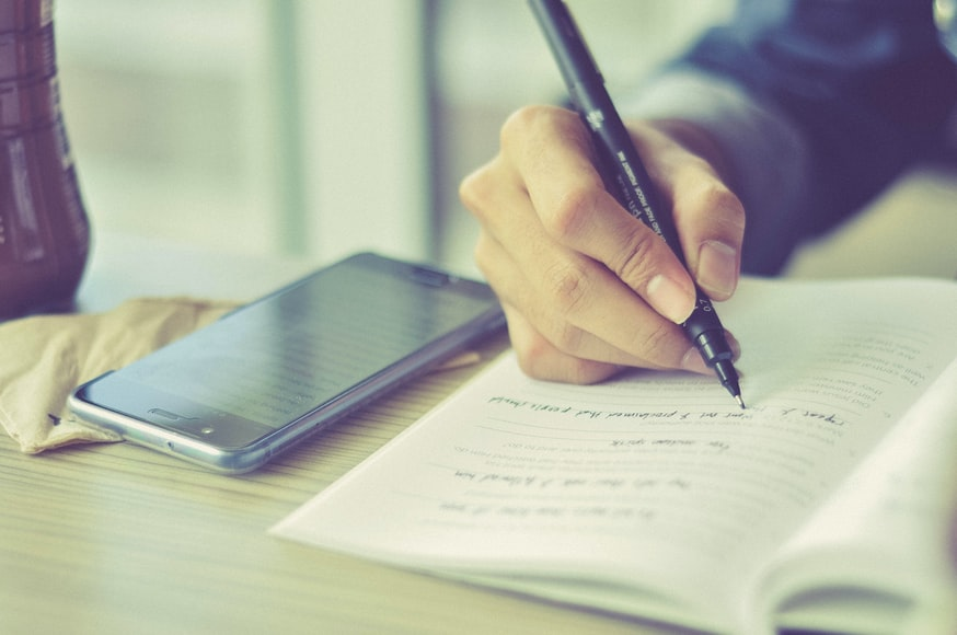 Mão escrevendo em um caderno com um celular ao lado.