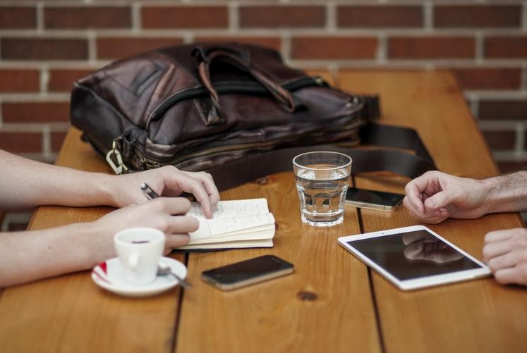 Na imagem, duas pessoas conversam em uma mesa de madeira. O cenário é de um reunião. Na mesa há elemento como: uma bolsa, bloco de papel, café, água e eletrônicos.