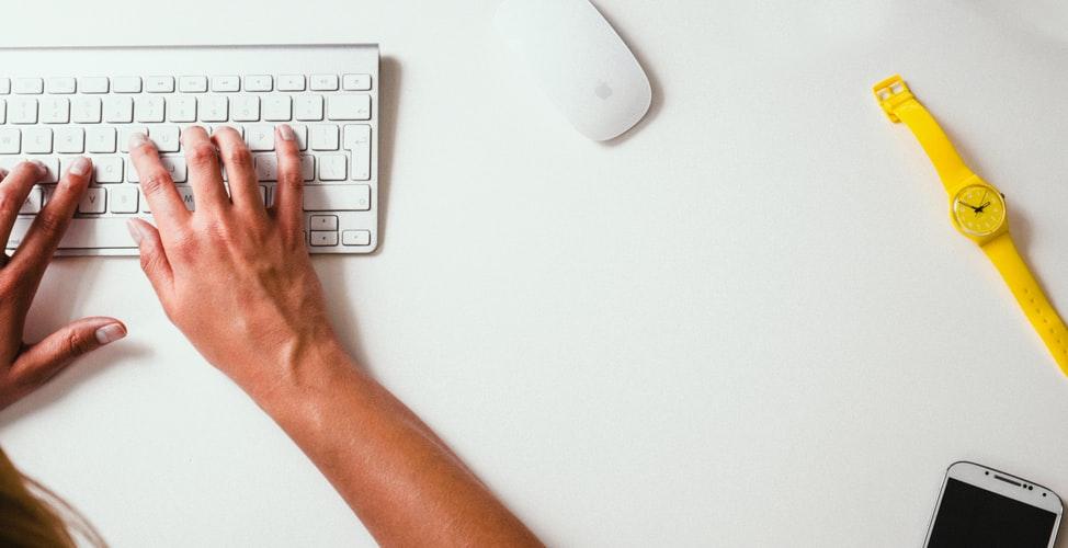 o-que-esperar-curso-administracao - Descrição da Imagem: mãos em um teclado. Ao lado, um mouse e um relógio amarelo.