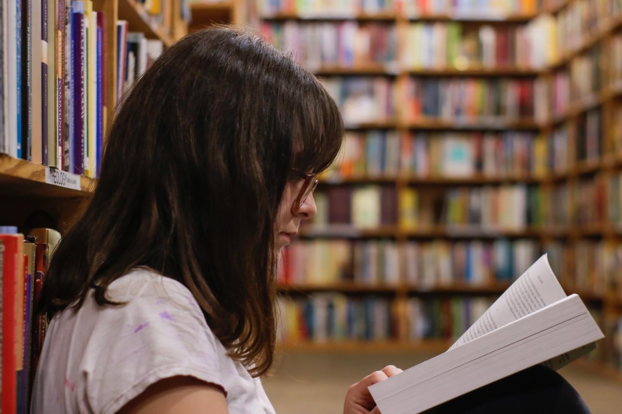 para-mim-ou-para-eu - mulher lendo livro em biblioteca
