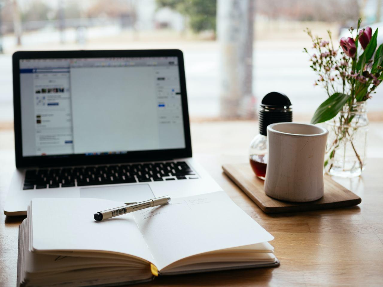 para-mim-ou-para-eu - mesa com notebook, caderno aberto e xícara