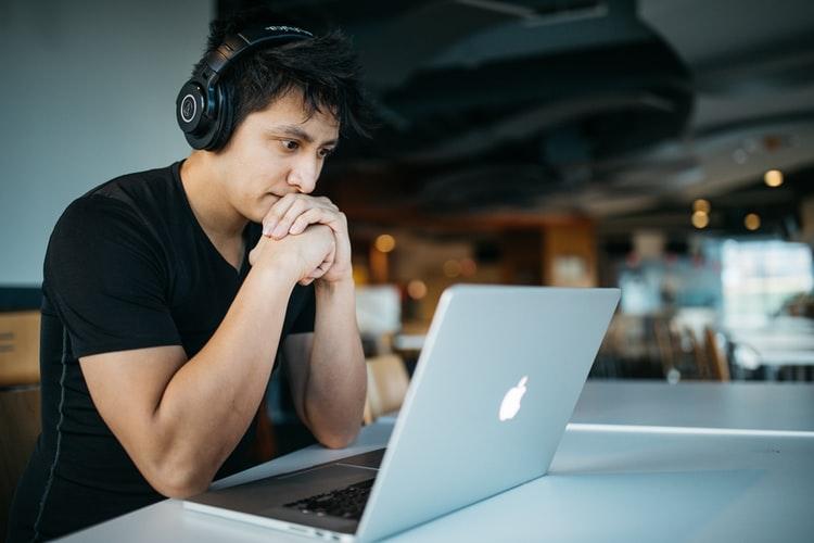 Menino olhando para um notebook. Ele está usando fones de ouvido.