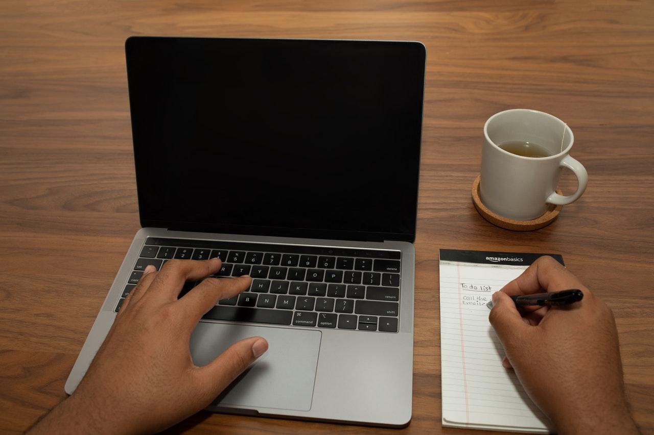 mãos teclando em um notebook e escrevendo em um bloco.